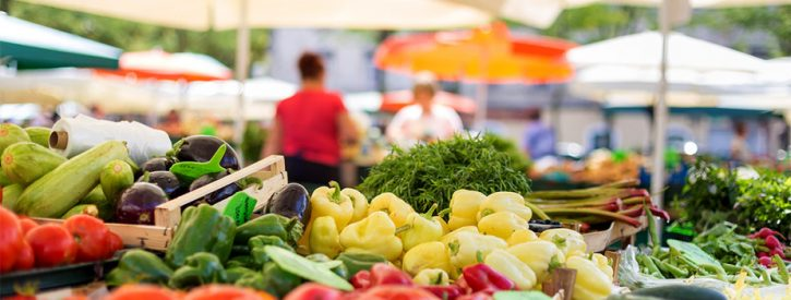 zucchini, tomatoes, bell peppers, eggplant, rhubarb, beans in the foreground, people buying and selling under umbrellas in soft focus in the background